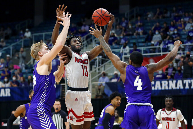 Nicholls State guard Andre Jones (13) shoots between Abilene Christian center Kolton Kohl, left, and guard Damien Daniels (4) during the second half of an NCAA college basketball game for the Southland Conference men's tournament championship Saturday, March 13, 2021, in Katy, Texas. (AP Photo/Michael Wyke)