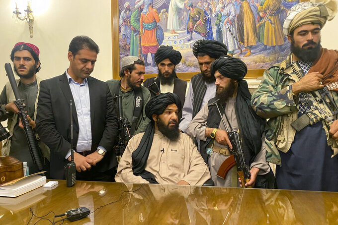 FILE - In this Sunday, Aug. 15, 2021 file photo, Taliban fighters take control of Afghan presidential palace after the Afghan President Ashraf Ghani fled the country, in Kabul, Afghanistan. Person second from left is a former bodyguard for Ghani. (AP Photo/Zabi Karimi)