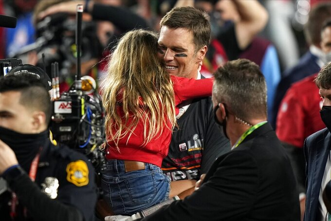 Tampa Bay Buccaneers quarterback Tom Brady and his daughter embrace after the NFL Super Bowl 55 football game, Sunday, Feb. 7, 2021, in Tampa, Fla. The Buccaneers defeated the Chiefs 31-9 to win the Super Bowl. (AP Photo/David J. Phillip)