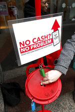 In this Friday, Nov. 15, 2019, photo, a shopper donates cash to the Salvation Army's annual holiday red kettle campaign, with a reminder that mobile contributions are also excepted on Chicago's Magnificent Mile. Cashless shoppers have a new option to give to the Army's red kettle campaign this year using their smartphone. Leaders hope adding Apple and Google payment options will boost fundraising to the campaign, which makes up 10% of The Salvation Army's annual budget. Those donations fund programs providing housing, food and other support to people in poverty. (AP Photo/Charles Rex Arbogast)