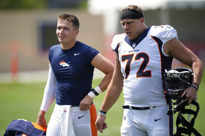 Denver Broncos quarterback Drew Lock, left, and offensive tackle Garett Bolles talk as they head to the locker room after taking part in drills at an NFL football training camp practice Tuesday, Aug. 3, 2021, at team headquarters in Englewood, Colo. (AP Photo/David Zalubowski)