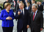German Chancellor Angela Merkel, left, greets United Nations Secretary General Antonio Guterres, right, and Russian President Vladimir Putin, center, during arrivals for a conference on Libya at the chancellery in Berlin, Germany, Sunday, Jan. 19, 2020. German Chancellor Angela Merkel hosts the one-day conference of world powers on Sunday seeking to curb foreign military interference, solidify a cease-fire and help relaunch a political process to stop the chaos in the North African nation. (AP Photo/Jens Meyer)