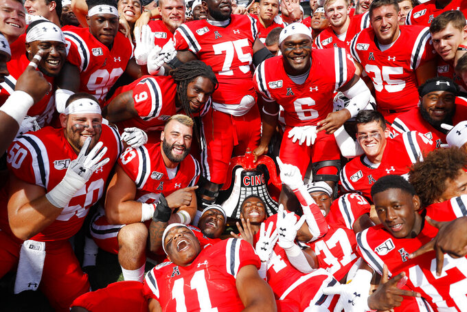 Cincinnati players celebrates with the victory bell after defeating Miami of Ohio in an NCAA college football game, Saturday, Sept. 14, 2019, in Cincinnati. (AP Photo/John Minchillo)