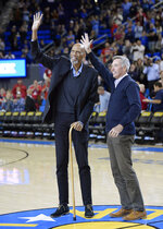 Members of the 1968-69 UCLA basketball team Kareem Abdul-Jabbar, left, and Lynn Shackelford wave to fans as they and several other members of the team were introduced during halftime of UCLA's NCAA college basketball game against Arizona on Saturday, Jan. 26, 2019, in Los Angeles. (AP Photo/Mark J. Terrill)