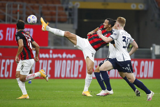 AC Milan's Zlatan Ibrahimovic controls the ball by Bologna's Jerdy Schouten during the Serie A soccer match between AC Milan and Bologna at the San Siro stadium, in Milan, Italy, Monday, Sept. 21, 2020. (AP Photo/Antonio Calanni)