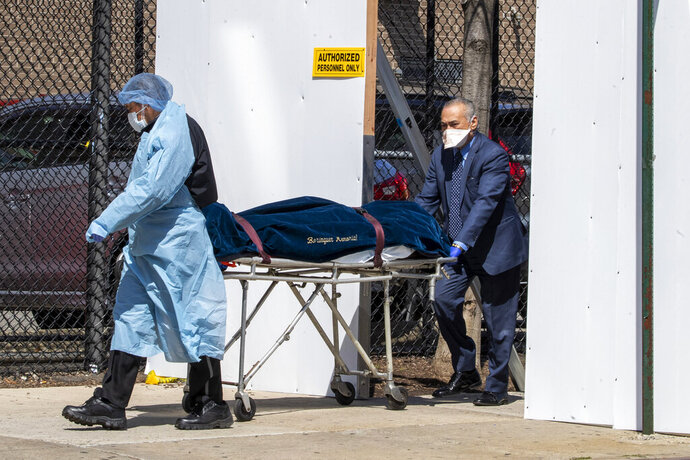 A funeral director and a Wycoff Heights Medical Center, employee transport a body, Wednesday, April 1, 2020, in New York. The new coronavirus causes mild or moderate symptoms for most people, but for some, especially older adults and people with existing health problems, it can cause more severe illness or death. (AP Photo/Mary Altaffer)