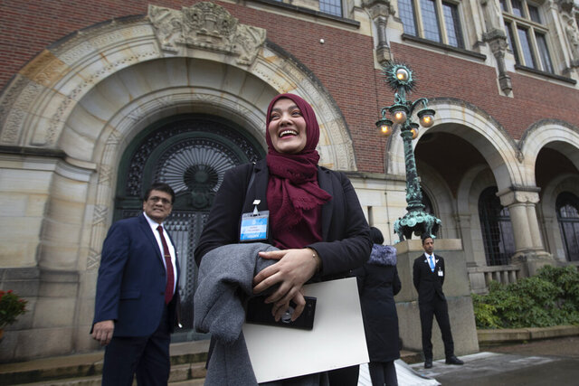 Yasmin Ullah, a member of the Rohingya community, is all smiles as she walks out of the International Court in The Hague, Netherlands, Thursday, Jan. 23, 2020, after the court ordered Myanmar take all measures in its power to prevent genocide against the Rohingya. The United Nations' top cour issued a decision on a request by Gambia. (AP Photo/Peter Dejong)