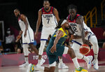 United States's Jrue Holiday (12), right, knocks the ball away from Australia's Patty Mills (5), front, during men's basketball semifinal game at the 2020 Summer Olympics, Thursday, Aug. 5, 2021, in Saitama, Japan. (AP Photo/Eric Gay)