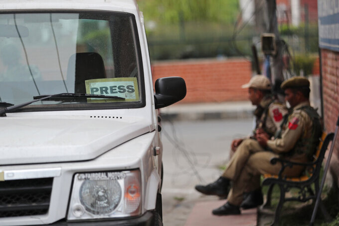 Indian policemen rest on a bench at the entrance of Press Enclave, which houses several newspaper offices, in Srinagar, Indian-controlled Kashmir, Wednesday, Sept. 8, 2021. Police raided the homes of four journalists on Wednesday, triggering concerns of a further crackdown on press freedom in the disputed region. After the raids in Srinagar, the region's main city, the four journalists were summoned to local police stations where they were questioned. Police did not specify the reason for the raids. (AP Photo/Mukhtar Khan)