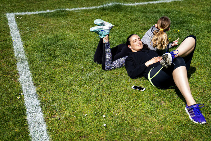 Livia and Lorenza enjoy the sun with their daughter Sara at Islands Brygge in Copenhagen on Sunday, May 3, 2020. Marked areas on the grassland help people keep distance from each other, with about 40 m2 area marked out for a maximum of 10 people, to limit the spread of coronavirus infection, seen with 48 mm telephoto lens. (Ida Guldbaek Arentsen / Scanpix via AP)