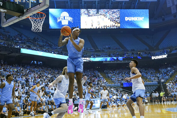 North Carolina's Armando Bacot, center foreground, grabs a rebound during the NCAA college basketball team's season opening event and scrimmage in Chapel Hill, N.C., Friday, Oct. 15, 2021. (AP Photo/Gerry Broome)