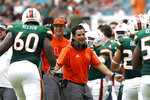 Miami head coach Manny Diaz, center, greets Miami offensive lineman Zion Nelson (60) and running back Cody Brown after Brown scored a touchdown during the first half of an NCAA college football game against Central Connecticut State, Saturday, Sept. 25, 2021, in Miami Gardens, Fla. (AP Photo/Lynne Sladky)