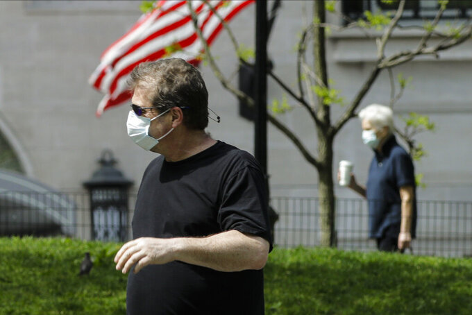 People wear protective masks in Central Park during the coronavirus pandemic Saturday, May 16, 2020, in New York. (AP Photo/Frank Franklin II)