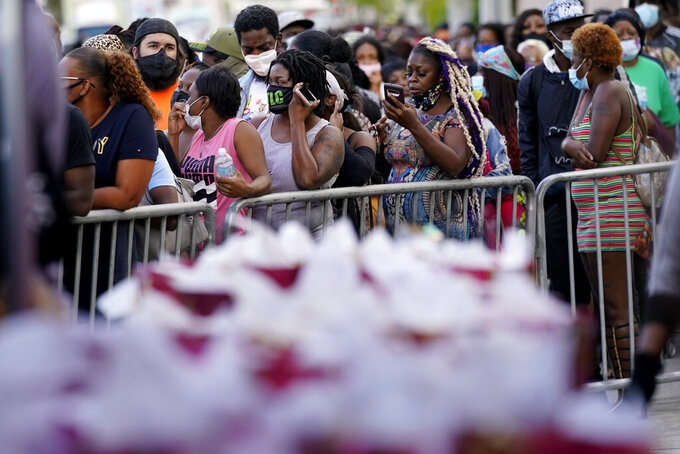 """Residents in the Overtown neighborhood of Miami wait in line to receive gift cards and gift bags with essentials, Tuesday, Dec. 29, 2020. Various organizations came together to distribute items to those in need during the coronavirus pandemic. Rapper Sean """"Diddy"""" Combs also passed out fifty dollar bills to residents. (AP Photo/Lynne Sladky)"""