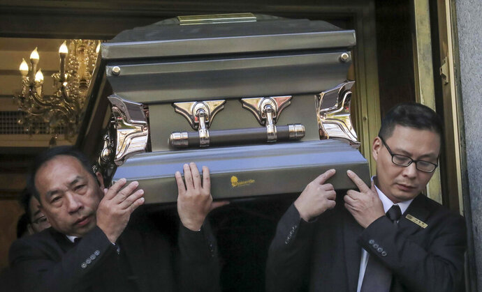 REMOVES REFERENCE TO HOMELESS KILLED  - Pallbearers carry the casket of Chuen Kok from the Ng Fook Funeral Home, Friday Oct. 18, 2019, in New York. Kok, an 83-year-old homeless man whom Chinatown residents warmly greeted as