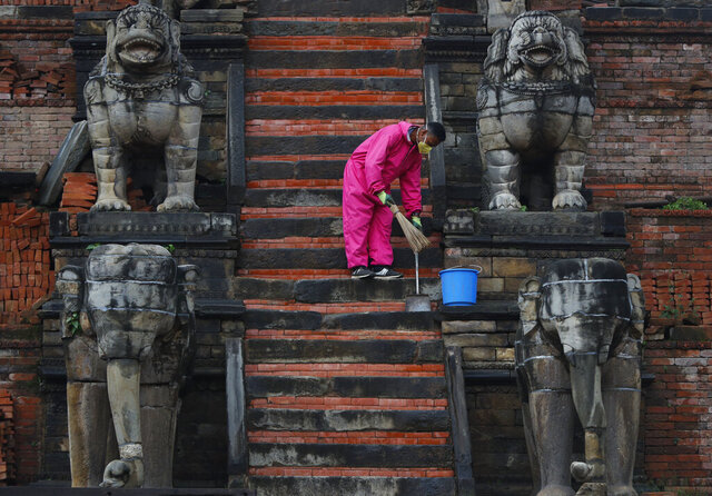A Nepalese cleaner sweeps the stairs of temple during lockdown in Bhaktapur, Nepal, Tuesday, May 26, 2020. Nepal's lockdown imposed on March 24 to stop the spread of the coronavirus has been extended to June 2. (AP Photo/Niranjan Shrestha)