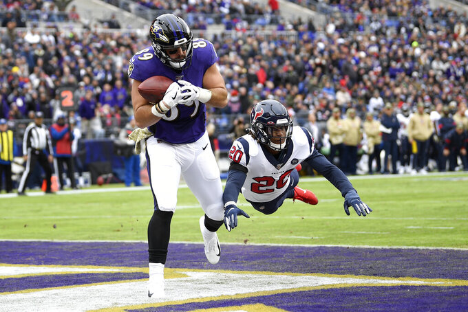 Baltimore Ravens tight end Mark Andrews (89) catches a touchdown pass from quarterback Lamar Jackson, not visible, as Houston Texans strong safety Justin Reid (20) dives to try to stop him during the first half of an NFL football game, Sunday, Nov. 17, 2019, in Baltimore. (AP Photo/Nick Wass)