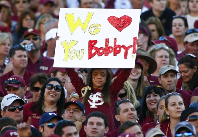 FILE - In this Oct. 26, 2013, file photo, a fan holds up a sign in support of former Florida State head coach Bobby Bowden in the second quarter of an NCAA college football game against North Carolina State in Tallahassee, Fla. Bowden, the folksy Hall of Fame coach who built Florida State into an unprecedented college football dynasty, has died. He was 91. Bobby's son, Terry, confirmed to The Associated Press that his father died at home in Tallahassee, Fla., surrounded by family early Sunday, Aug. 8, 2021. (AP Photo/Phil Sears, File)