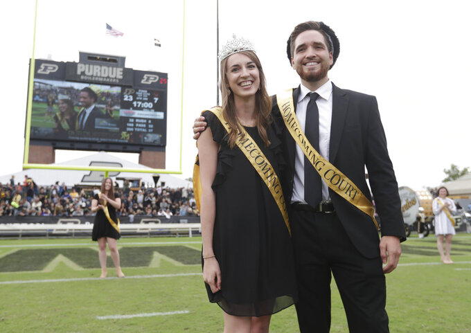 "Grant Wood and Lily Bishop pose after being named ""Royalty"" as part of Purdue's first gender-neutral homecoming court during halftime of an NCAA college football game between Purdue and Boston College in West Lafayette, Ind., Saturday, Sept. 22, 2018. The school eliminated the titles of king and queen and students cast two votes for ""royalty"". (AP Photo/Michael Conroy)"