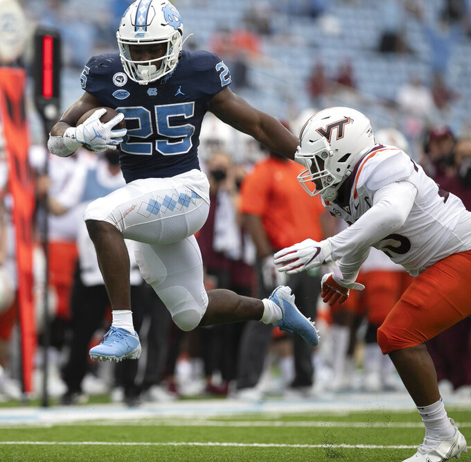 FILE - In this Oct. 10, 2020, file photo, North Carolina's Javonte Williams (25) breaks away from Virginia Tech's Rayshard Ashby (23) on a 19-yard run for a touchdown during an NCAA college football game at Kenan Stadium in Chapel Hill, N.C. Williams' 25th-ranked Tar Heels host No. 2 Notre Dame on Friday. (Robert Willett/The News & Observer via AP, File)