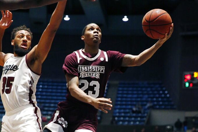 Mississippi State guard Tyson Carter (23) attempts a layup past New Mexico State forward Johnny McCants (35) during the second half of an NCAA college basketball game, Sunday, Dec. 22, 2019, in Jackson, Miss. (AP Photo/Rogelio V. Solis)