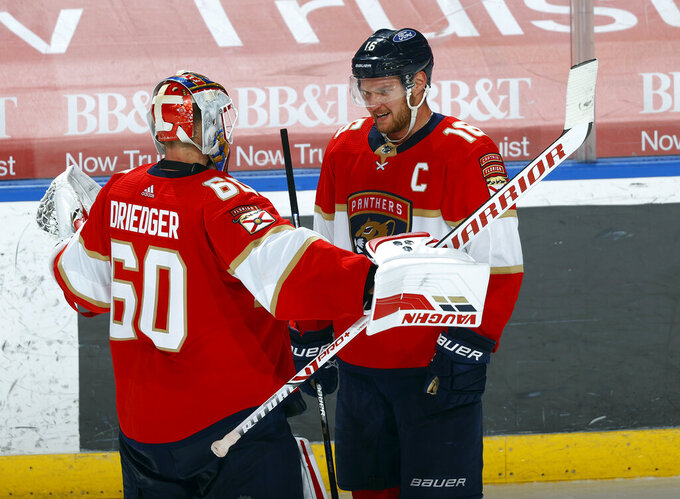 Florida Panthers goaltender Chris Driedger (60) celebrates with center Aleksander Barkov (16), who scored in overtime of the team's NHL hockey game against the Carolina Hurricanes, Saturday, April 24, 2021, in Sunrise, Fla. (AP Photo/Joel Auerbach)