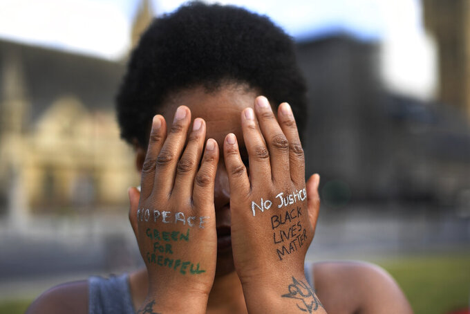 "FILE - In this file photo dated Sunday, June 21, 2020, a woman symbolically covers her eyes as she participates in a Black Lives Matter protest calling for an end to racial injustice, at the Parliament Square in central London.  A government inquiry, by a panel of experts, has concluded Wednesday March 31, 2021, that there is racism in Britain, but it's not a systematically racist country that is ""rigged"" against non-white people, though many ethnic-minority Britons greeted that claim with skepticism.  (AP Photo/Alberto Pezzali)"