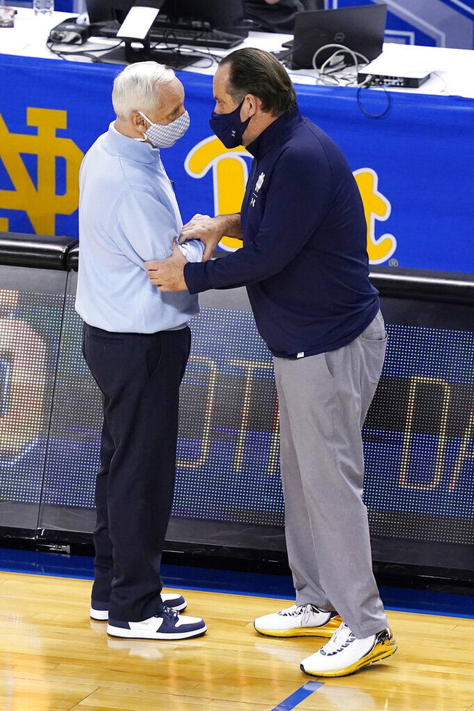 North Carolina head coach Roy Williams, left, greets Notre Dame head coach Mike Brey after an NCAA college basketball game in the second round of the Atlantic Coast Conference tournament in Greensboro, N.C., Wednesday, March 10, 2021. UNC won the game 101-59. (AP Photo/Gerry Broome)