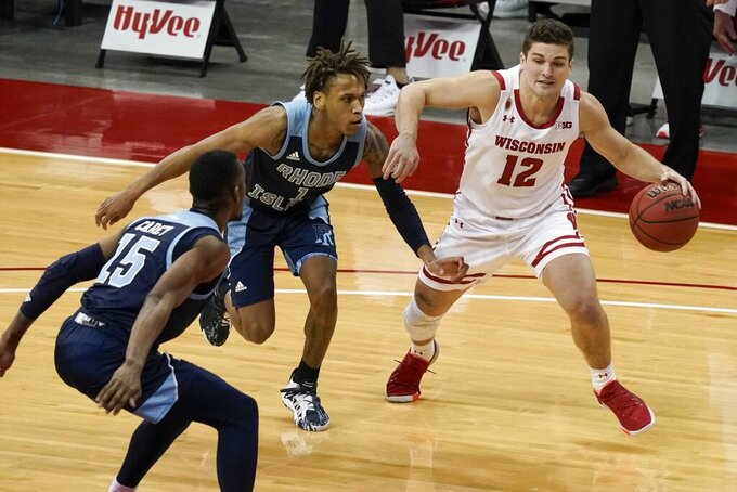Wisconsin's Trevor Anderson tries to drive past Rhode Island's Jalen Carey (15) and Fatts Russell (1) during the second half of an NCAA college basketball game Wednesday, Dec. 9, 2020, in Madison, Wis. (AP Photo/Morry Gash)