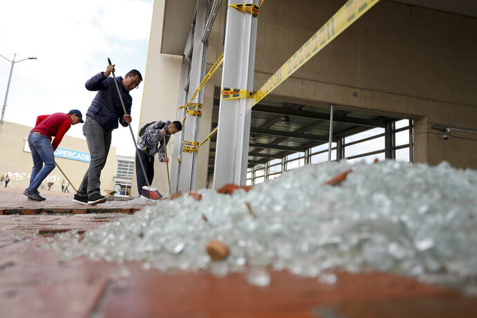 Workers clear broken glass from a bus station damaged by anti-government demonstrators, in Bogota, Colombia, Friday, Nov. 22, 2019. Protesters attacked the station Thursday during a nationwide strike called by labor unions, students and teachers to protest everything from economic inequality to violence against social leaders. (AP Photo/Fernando Vergara)