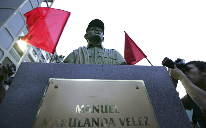FILE - In this Sept. 26, 2008 file photo, photographers take pictures of a bust of the late Manuel Marulanda, the founding leader of the Revolutionary Armed Forces of Colombia, or FARC, unveiled by members of the Venezuela's Communist Party in a plaza in the Caracas' 23 de Enero neighborhood of Caracas, Venezuela. Colombian news magazine Semana reported on Sunday, Sept. 8, 2019 that leaked intelligence reports indicate Venezuelan President Nicolas Maduro's socialist government is harboring Colombian rebels inside Venezuela, and Colombian officials say the information coincides with allegations they will present in Sept. 2019 to the U.N. (AP Photo/Fernando Llano, File)