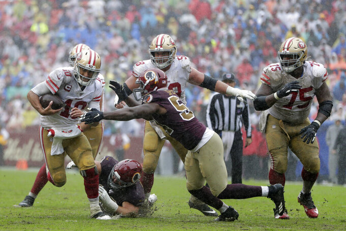 San Francisco 49ers quarterback Jimmy Garoppolo, left, attempts to rush past Washington Redskins defensive end Noah Spence, center, in the second half of an NFL football game, Sunday, Oct. 20, 2019, in Landover, Md. (AP Photo/Julio Cortez)