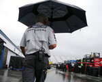 A NASCAR official walks through the garage area in the rain before the NASCAR Cup Series auto race Sunday, July 22, 2018, at New Hampshire Motor Speedway in Loudon, N.H. (AP Photo/Mary Schwalm)