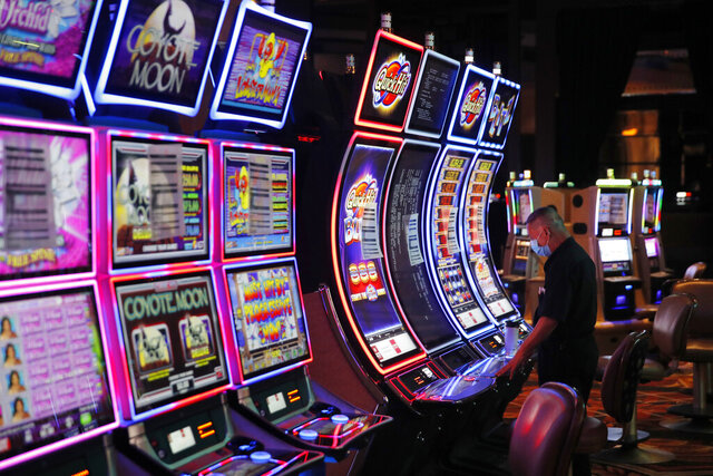 FILE - In this May 21, 2020, file photo, a worker looks over an electronic slot machine as chairs have been removed from some machines to maintain social distancing between players at a closed Caesars Palace hotel and casino in Las Vegas. Cards will be cut, dice will roll and jackpots jingle when casinos in Las Vegas and Nevada begin reopening at 12:01 a.m. Thursday, June 4. There will be big splashes, even amid ongoing unrest, and big hopes for recovery from an unprecedented and expensive closure prompted by the coronavirus pandemic. (AP Photo/John Locher, File)