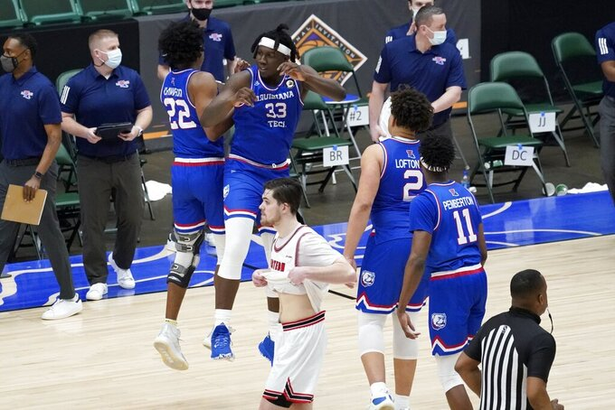 Western Kentucky guard Luke Frampton, front center, walks to the bench as Louisiana Tech's Isaiah Crawford (22), Andrew Gordon (33), Kenneth Lofton Jr. (2) and JaColby Pemberton (11) celebrate the team's win in an NCAA college basketball game in the quarterfinals of the NIT, Thursday, March 25, 2021, in Frisco, Texas. (AP Photo/Tony Gutierrez)