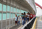 FILE - In this June 28, 2019 file photo, local residents with visas walk across the Puerta Mexico international bridge to enter the U.S., in Matamoros, Tamaulipas state, Mexico. A U.S. judge in Oregon on Tuesday, Nov. 26, 2019, granted a preliminary injunction blocking a Trump administration proclamation that would require immigrants to show proof of health insurance to get a visa. (AP Photo/Rebecca Blackwell, File)