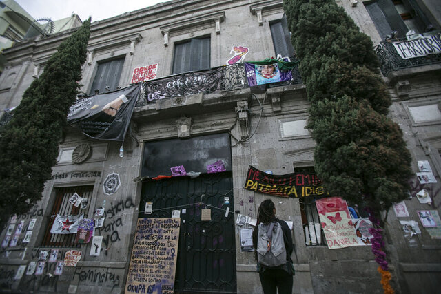A woman looks at the Mexico's Human Rights Commission (CNDH) headquarters which has been occupied for almost three months by women's rights activists who have converted it into a refuge for victims of gender violence in Mexico City, Tuesday, Nov. 17, 2020. Feminist activists are occupying the building to demand justice for the victims of sexual abuse, femicide, and other gender violence, and are hosting some women and their children after the government either failed to solve or investigate sexual attacks on their guest's daughters. (AP Photo/Ginnette Riquelme)