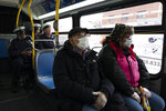 Passengers wear masks while riding a city bus during the coronavirus pandemic, Wednesday, March 25, 2020 in the Brooklyn borough of New York. Police have stepped up efforts to pressure New Yorkers to practice social distancing at the epicenter of the crisis. It's part of a global challenge that law enforcement and health officials say is critical to containing the coronavirus. (AP Photo/Mark Lennihan)