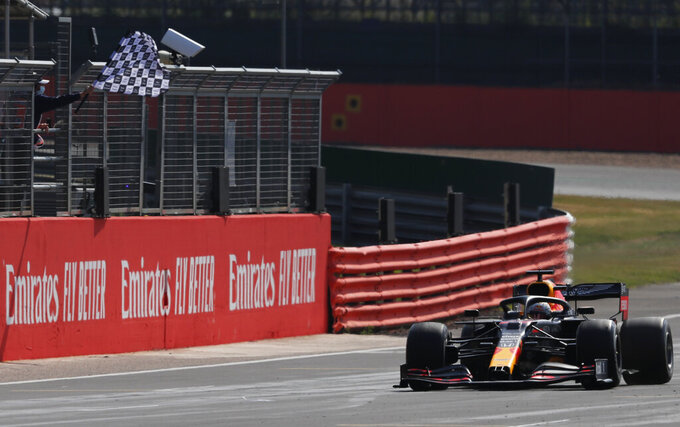 Red Bull driver Max Verstappen of the Netherlands passes the checkered flag to take first place during the 70th Anniversary Formula One Grand Prix at the Silverstone circuit, Silverstone, England, Sunday, Aug. 9, 2020. (AP Photo/Frank Augstein, Pool)