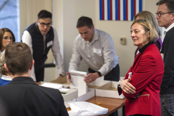 Alaska House District 1 candidate Democrat Kathryn Dodge, right, watches the election recount at the Department of Elections' Juneau office on Friday, Nov. 30, 2018. A single mystery ballot found on a precinct table on Election Day but not counted then could decide a tied Alaska state House race and thwart Republican efforts to control the chamber and all of state government. The ballot arrived in Juneau last Friday in a secrecy sleeve in a bin with other ballot materials. Officials were investigating its origins and handling before deciding whether to tally it. (Michael Penn/The Juneau Empire via AP)