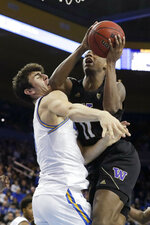 UCLA guard Jaime Jaquez Jr., left, fouls Washington guard Nahziah Carter during the second half of an NCAA college basketball game in Los Angeles, Saturday, Feb. 15, 2020. (AP Photo/Chris Carlson)