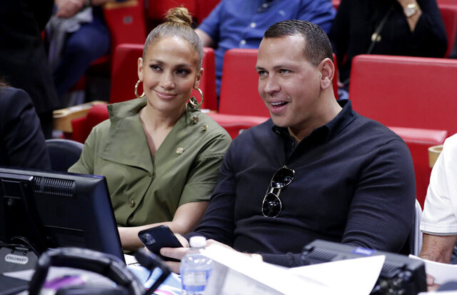 FILE - In this Dec. 13, 2019, file photo, Jennifer Lopez, left, and Alex Rodriguez sit courtside during an NBA basketball game between the Miami Heat and the Los Angeles Lakers in Miami. Rodriguez and Lopez have retained J.P. Morgan to represent them in raising capital for a possible bid for the New York Mets. The move was first reported by Variety and confirmed to The Associated Press by a person familiar with the decision who spoke on condition of anonymity because it was not announced. (AP Photo/Lynne Sladky, File)