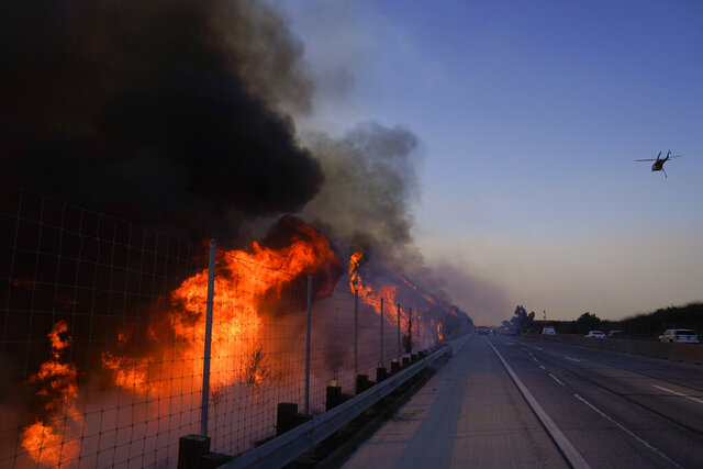 The Blue Ridge Fire burns along the 71 state highway Tuesday, Oct. 27, 2020, in Chino Hills, Calif. Crews tried to beat back two out-of-control wildfires in Southern California on Tuesday that have kept tens of thousands of people out of their homes even as another round of dangerous fire weather raises the risk for flames erupting across the state. (AP Photo/Jae C. Hong)