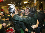 Oakland Athletics' Matt Joyce, center, is doused in the clubhouse celebration after clinching a wild card spot after the baseball game against the Seattle Mariners, Monday, Sept. 24, 2018, in Seattle. (AP Photo/John Froschauer)