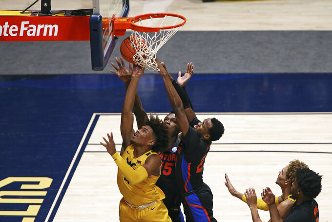 West Virginia guard Miles McBride (4) shoots while defended by Florida forward Osayi Osifo (15) and guard Scottie Lewis (23) during the first half of an NCAA college basketball game Saturday, Jan. 30, 2021, in Morgantown, W.Va. (AP Photo/Kathleen Batten)