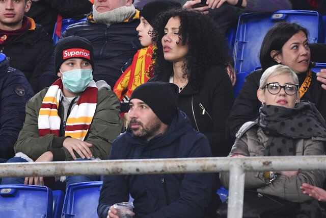 An AS Roma fan wears a sanitary mask as he watches the Italian Serie A soccer match between Roma and Lecce at the Olympic stadium in Rome, Sunday, Feb. 23, 2020. Four Serie A matches were postponed in Northern Italy for concern on possible spreading of the COVID-19 viral illness. (Alfredo Falcone/LaPresse via AP)
