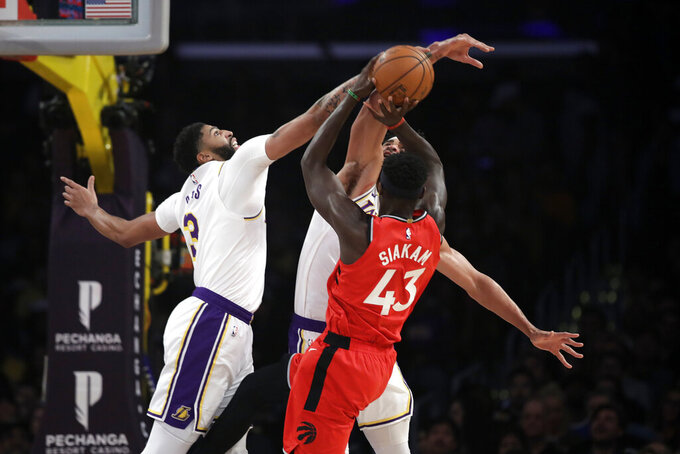 Los Angeles Lakers' Anthony Davis, left, blocks a shot from Toronto Raptors' Pascal Siakam (43) during the first half of an NBA basketball game Sunday, Nov. 10, 2019, in Los Angeles. (AP Photo/Marcio Jose Sanchez)