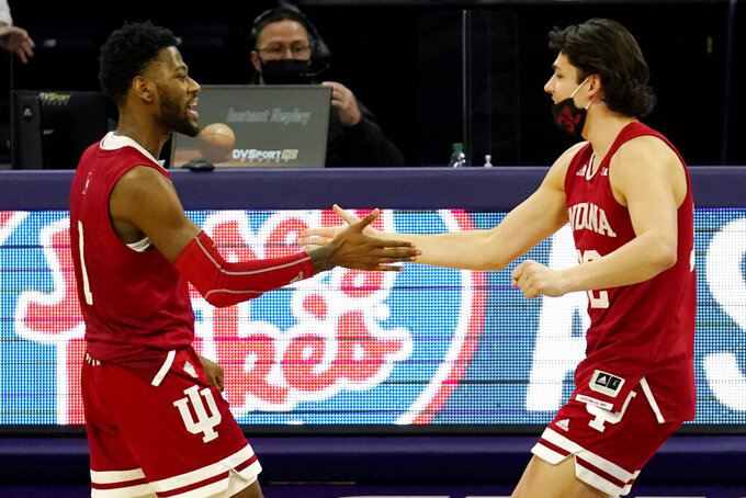 Indiana guard Al Durham, left, celebrates with guard Trey Galloway after Indiana defeated Northwestern 79-76 after double overtime of an NCAA college basketball game in Evanston, Ill., Wednesday, Feb. 10, 2021. (AP Photo/Nam Y. Huh)