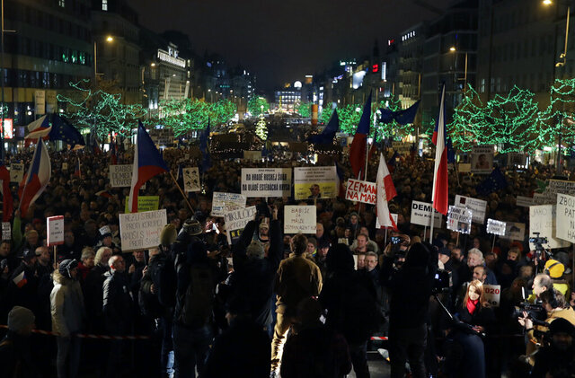 People hold placards calling for the resignation of Czech Republic's Prime Minister Andrej Babis, as thousands of demonstrators gather to demand his resignation at the Wenceslas square in Prague, Czech Republic, Tuesday, Dec. 17, 2019. Babis faces legations that he has misused EU subsidies for a farm he transferred to his family members, though he denies wrongdoing. (AP Photo/Petr David Josek)