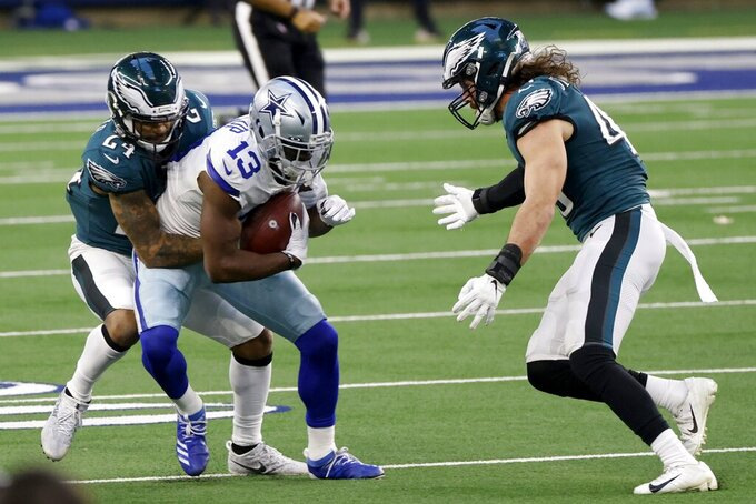 Dallas Cowboys wide receiver Michael Gallup (13) catches a pass for a first down as Philadelphia Eagles cornerback Darius Slay (24) and Alex Singleton (49) combine to make the stop in the first half of an NFL football game in Arlington, Texas, Sunday, Dec. 27. 2020. (AP Photo/Ron Jenkins)